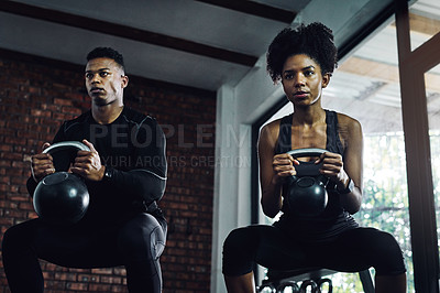 Buy stock photo Shot of a young man and woman working out with kettle bells in a gym