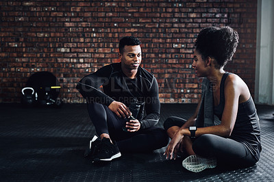 Buy stock photo Shot of a young man and woman chatting during a break at the gym