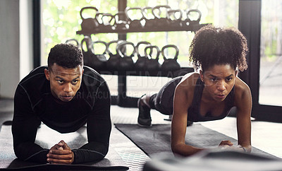 Buy stock photo Shot of a young man and woman doing plank exercises together in a gym