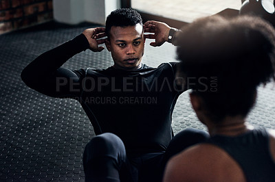 Buy stock photo Shot of a young woman helping a man do sit ups at the gym