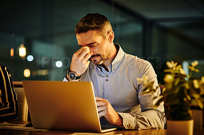 Buy stock photo Shot of a mature businessman looking stressed out while working in an office at night