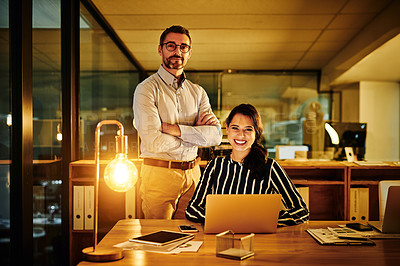 Buy stock photo Portrait of two businesspeople working together in an office at night