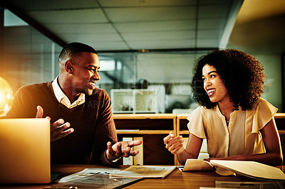 Buy stock photo Cropped shot of two young businesspeople sitting together and having a discussion in the office late at night