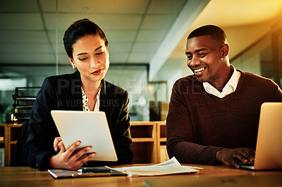 Buy stock photo Cropped shot of two young businesspeople sitting together and using technology during a discussion in the office at night