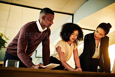 Buy stock photo Cropped shot of a diverse group of businesspeople standing together and brainstorming in the office late at night