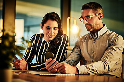 Buy stock photo Shot of a businessman showing his colleague something on his cellphone in an office at night