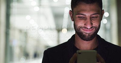 Buy stock photo Cropped shot of a handsome young businessman standing and texting on his cellphone after working late in the office