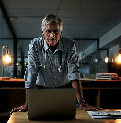 Buy stock photo Portrait of a mature male doctor working on a laptop inside his office at night