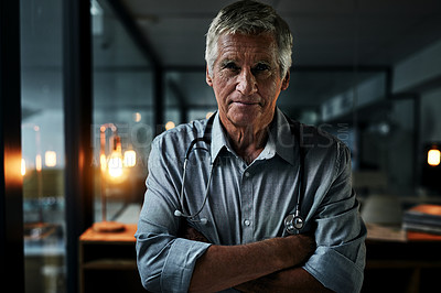 Buy stock photo Portrait of a mature male doctor posing with his arms folded inside his office at night