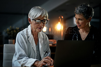 Buy stock photo Shot of two experienced female medical professionals working on a laptop together inside their office at a hospital at night