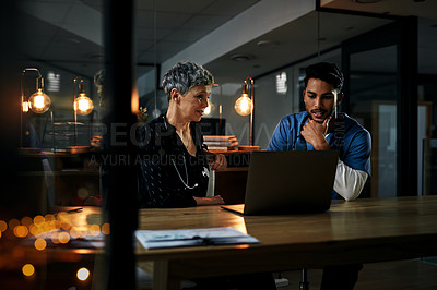 Buy stock photo Shot of two medical professionals working on a laptop together inside their office at a hospital at night