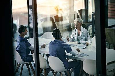 Buy stock photo Shot of a group of medical professionals having a meeting together inside a boardroom at a hospital