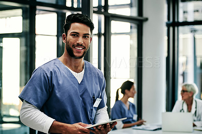 Buy stock photo Shot a handsome young male nurse using a digital tablet inside a hospital