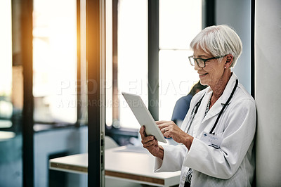 Buy stock photo Shot of a mature female doctor using a digital tablet inside a hospital