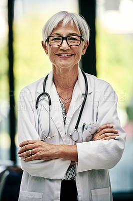 Buy stock photo Portrait of a cheerful mature female doctor posing with a her arms folded inside a hospital