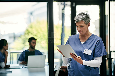 Buy stock photo Shot of a mature female nurse using a digital tablet at a hospital with her colleagues in the background