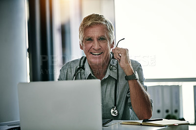 Buy stock photo Portrait of a handsome mature doctor working on a laptop inside his office