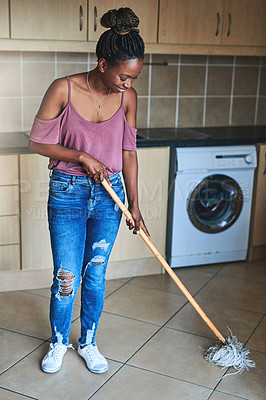 Buy stock photo Shot of a young woman mopping her floors at home