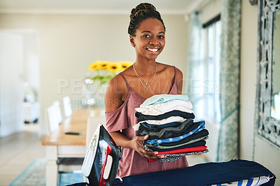 Buy stock photo Cropped shot of a young woman ironing her washed clothes at home