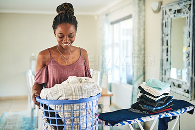 Buy stock photo Cropped shot of a young woman getting ready do iron a basket full of clothes