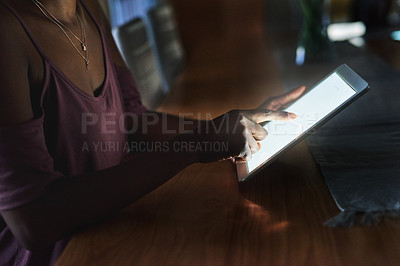 Buy stock photo Cropped shot of an unrecognizable woman using a digital tablet in the dark