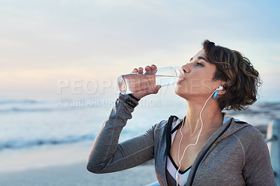 Buy stock photo Cropped shot of a young woman drinking water after her run