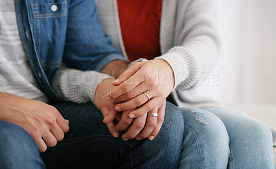 Buy stock photo Cropped shot of an unrecognizable couple sitting together at home