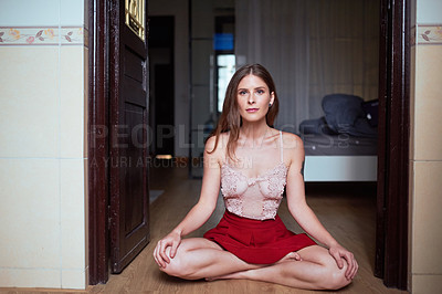 Buy stock photo Full length shot of an attractive young woman sitting down and meditating inside her apartment
