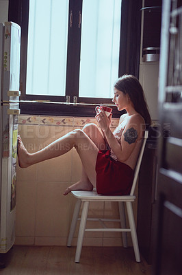 Buy stock photo Full length shot of an attractive young woman drinking coffee while sitting on a chair inside her kitchen at home