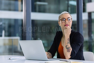 Buy stock photo Shot of a young businesswoman looking thoughtful while working on a laptop in an office