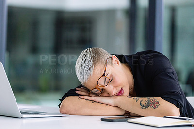 Buy stock photo Shot of a young businesswoman sleeping at a desk in an office