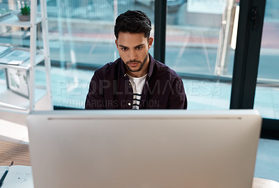 Buy stock photo Cropped shot of a handsome young businessman sitting alone in the office and working on his computer