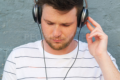 Buy stock photo Cropped shot of a handsome young man listening to music on his headphones outdoors