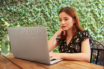 Buy stock photo Shot of an attractive young woman using her laptop while relaxing at an outdoor cafe