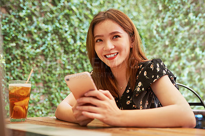 Buy stock photo Portrait of an attractive young woman using her cellphone while relaxing at an outdoor cafe