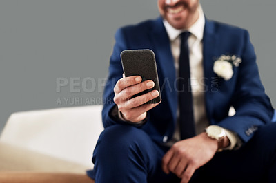 Buy stock photo Shot of an unrecognizable bridegroom using a cellphone while relaxing in the dressing room on his wedding day