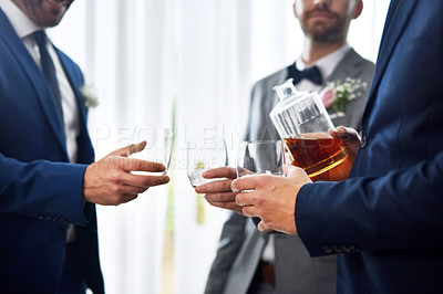 Buy stock photo Shot of two unrecognizable groomsmen sharing a toast with the bridegroom on his wedding day