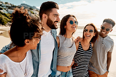Buy stock photo Shot of a group of happy young friends enjoying a summer's day at the beach