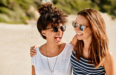 Buy stock photo Shot of two happy young women enjoying a summer's day at the beach