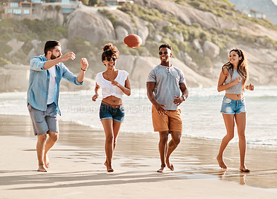 Buy stock photo Shot of a group of happy young friends playing catch with a ball at the beach