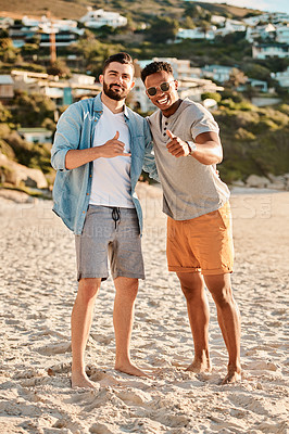 Buy stock photo Portrait of two happy young men enjoying a summer's day at the beach
