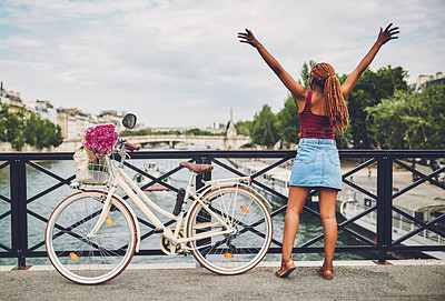 Buy stock photo Rearview shot of a young woman touring the city of Paris with a bicycle