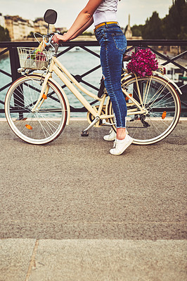 Buy stock photo Cropped shot of a young woman touring the city of Paris with a bicycle