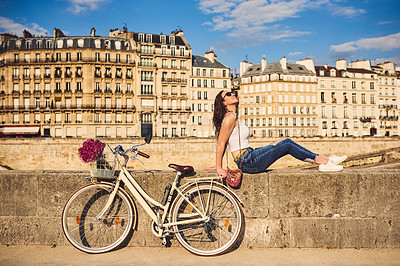 Buy stock photo Shot of a young woman listening to music while touring the city of Paris
