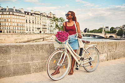 Buy stock photo Shot of a young woman touring the city of Paris with a bicycle