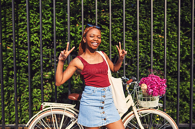 Buy stock photo Shot of a young woman making a peace gesture while touring the city of Paris with a bicycle