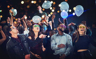 Buy stock photo Cropped shot of a diverse group of young friends having fun with balloons at a party at night