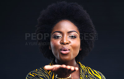 Buy stock photo Shot of a young woman blowing a kiss against a dark background