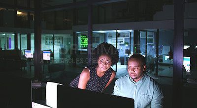 Buy stock photo Shot of two businesspeople working late at the office