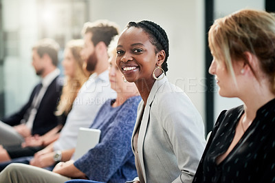 Buy stock photo Portrait of an attractive young businesswoman feeling cheerful while attending a business conference with other entrepreneurs